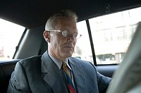Mature businessman reading newspaper in taxi