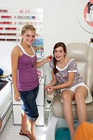 Two young women in beauty parlour, smiling, portrait