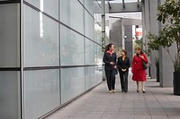 Three businesswomen walking outside a building and talking