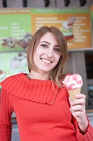 Portrait of a young woman holding an ice cream cone and smiling