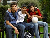 Three teenage boys 15-17 sitting on bench holding soccer ball outdoors