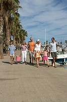 Three generation family with daughter 7-9 and son 11-13 walking by harbour