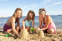 Three generations of women building sandcastles with daughter 7-9 at beach
