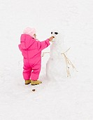 Girl 2-3 playing in snow, building snowman, rear view