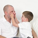 Father and son 3-5 playing, boy squashing man´s face