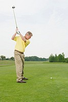 Golfer swinging to hit ball on golf course