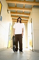 Man standing in hallway holding skateboard, low angle view
