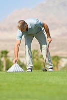 Mature man setting up tee in driving range