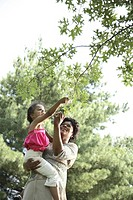 Mother lifting daughter 3-4 under tree