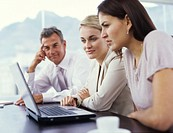 Businesswomen and man looking at laptop