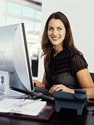 Young woman at desk using PC, smiling, portrait