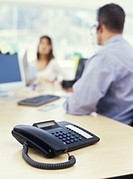 Office colleagues talking, telephone on desk
