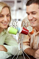 Couple looking at multi-coloured expresso cups hanging on rack in shop, close-up