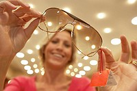 Woman holding pair of sunglasses in shop, portrait, focus on foreground, low angle view tilt