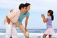 Two generation family standing on beach, girl 7-9 photographing parents, smiling, side view