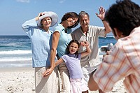 Man photographing three generation family on sandy beach, portrait, focus on background