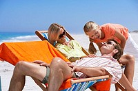 Family relaxing on beach, girl 9-11 bending over father, laughing, parents sitting in deckchairs