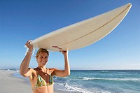 Young woman standing on beach, carrying surfboard on head, smiling, portrait, sea in background (thumbnail)