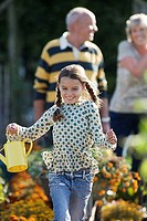 Girl 8-10 running in garden, holding watering can, smiling, grandparents standing in background
