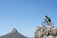 South Africa, male mountain biker standing at edge of rock, looking at view, profile