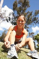 Woman tying trainer shoelace in park, sitting on grass, smiling, close-up, surface level tilt