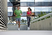 Couple jogging on urban elevated walkway, running side by side, smiling, front view, surface level