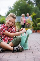Girl 7-9 sitting with watering can in garden centre, smiling, portrait, grandparents in background