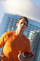 Man wearing orange t-shirt, jogging in city, listening to MP3 player strapped to arm, close-up tilt