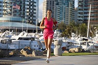USA, California, San Diego, woman wearing pink sports vest and shorts, jogging, listening to MP3 player strapped to arm, smiling, marina in background