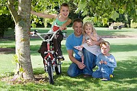 Father with three children 3-9 kneeling on grass beside tree in garden, girl sitting on bike, smiling, front view, portrait