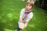 Blonde boy 8-10 wearing colourful striped scarf, holding bunch of wild mushrooms in field, smiling, portrait tilt