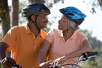 Active senior couple wearing cycling helmets and polo shirts, sitting on bicycles in park, face to face, smiling