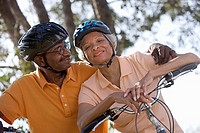Active senior couple wearing cycling helmets and polo shirts, sitting on bicycles in park, man embracing woman, smiling, portrait, low angle view tilt