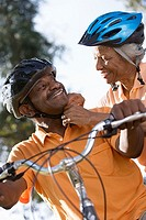 Active senior couple preparing to cycle in park, woman adjusting man´s cycling helmet strap, smiling, close-up, low angle view tilt