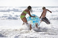 Three teenagers 13-15 playing with large inflatable beach ball in surf, laughing