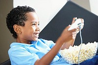 Boy 7-9 wearing blue polo shirt, playing on games console at home, bowl of popcorn in lap, smiling, side view, close-up
