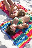 Two teenage girls 14-16 sunbathing on beach, text messaging on mobile phone, elevated view