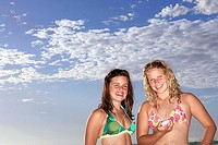 Two teenage girls 14-16 standing on beach in bikinis, listening to MP3 players, smiling, portrait