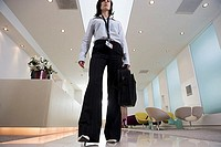 Businesswoman standing in lobby, carrying briefcase, front view, surface level