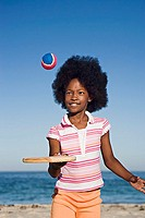Girl 8-10 playing with bat and ball on sandy beach, smiling, front view, portrait