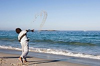 Boy 8-10 throwing sand and stone into sea, standing on beach at water's edge, rear view