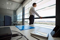 Businessman standing in office, looking through window, thinking, side view