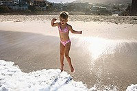 South Africa, Cape Town, girl 6-8 playing in surf at beach, resort in background