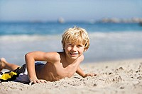 Blonde boy 7-9 lying on sandy beach, smiling, portrait