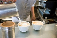 Waiter making two lattes, pouring milk from jug into cups, mid-section, close-up