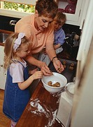 Grandmother and grandchildren 4-5 6-7 baking cookies, elevated view