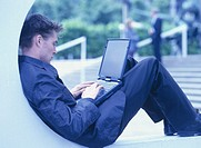 Young man using laptop, sitting on wall outdoors, side view