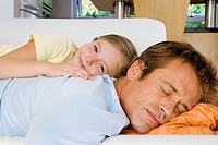 Father and daughter 7-9 lying on sofa at home, man sleeping, girl smiling, side view, close-up