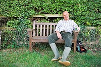 Senior man in wellington boots resting on bench in garden, smiling, front view, portrait