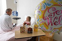 Girl 7-9 sitting in hospital bed, talking to doctor, balloon and cards in foreground, side view
